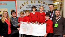 Children from Hope School receiving a cheque