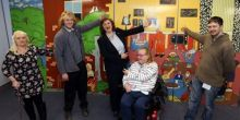 Three ladies, one in a wheelchair, and two men all laughing and pointing at the brightly coloured Heaths Houses artwork behind them