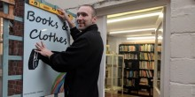 Stefan Laird, carpentry workshop supervisor for The Furniture Scheme, puts up a new sign for the bigger and better bookshop